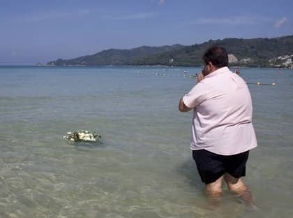 En man lägger blommor i vattnet i Phuket till minne av de som omkom i tsunamin för fem år sedan. Foto: David Longstreath/AP