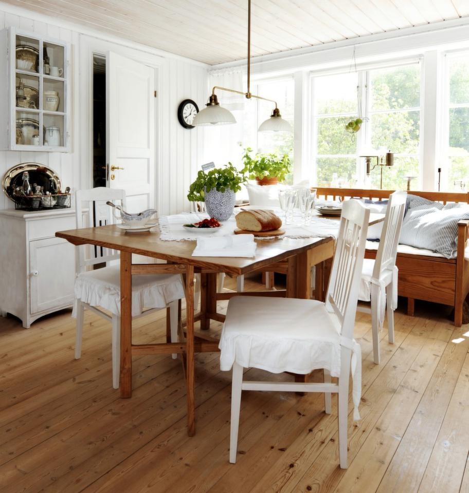 Det ljusa och luftiga köket med avlutade gamla allmogemöbler. På bordet står en prickig urna drejad av dottern Hanna Hagström Olén som är keramiker. Stolarna med överdrag från Nyblom & Kollén är arvegods. Det ljusa trägolvet är vitpigmenterat, såpat furugolv.
