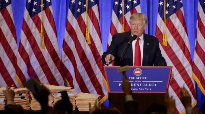 Donald Trump med de undertecknade pappren som låter hans söner ta över företagen. Foto: Seth Wenig / AP TT NYHETSBYRÅN