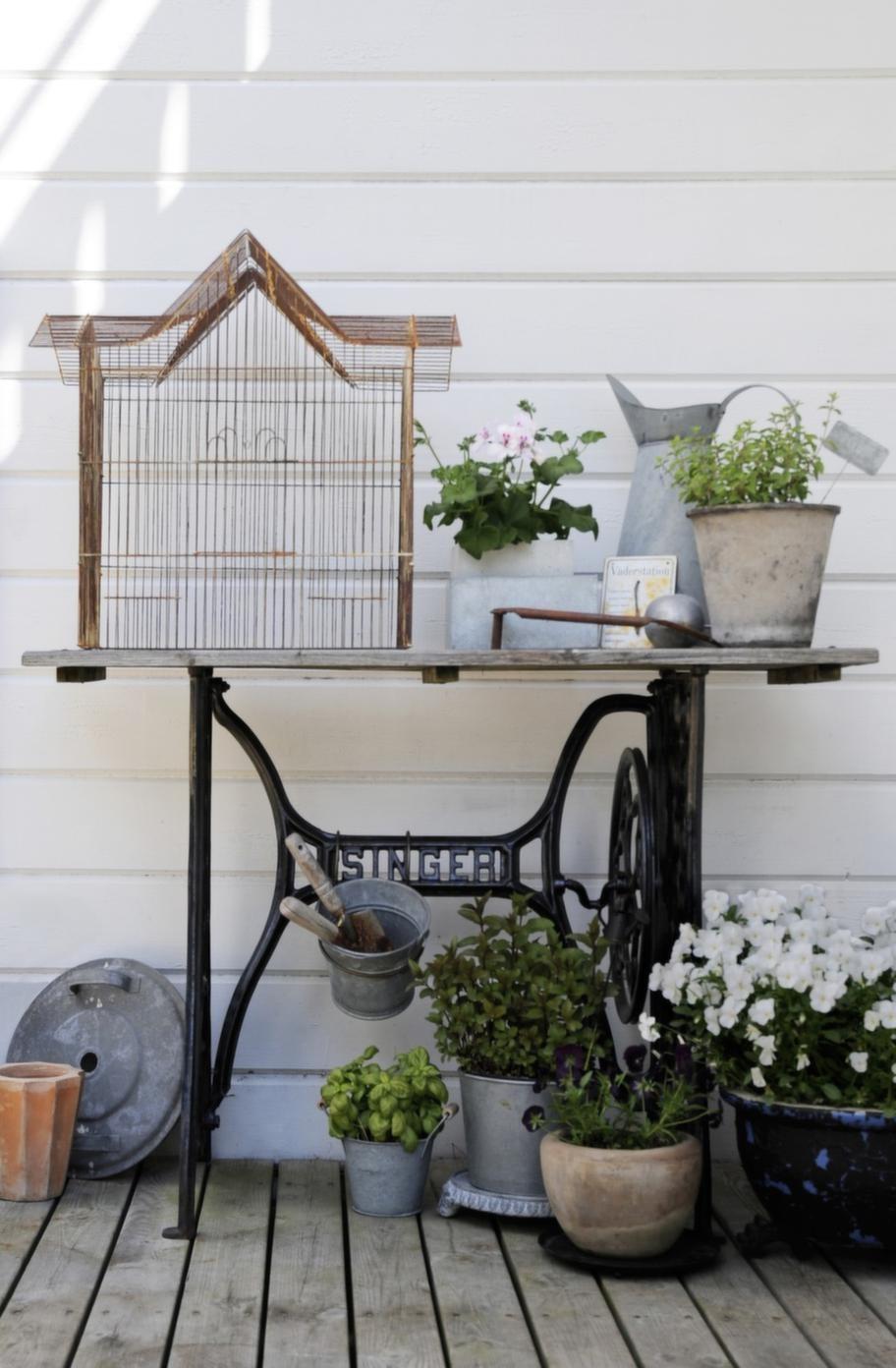 Ett gammalt symaskinsbord har blivit panteringsbord. Zinkkrukor blandat med krukor av keramik ger ett levande intryck. Fågelburen är köpt på loppis.