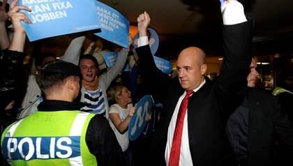 DEBATTSUCCÉ. Fredrik Reinfeldt lämnar SVT-huset efter gårdagens debatt. Utanför väntade hängivna anhängare och Reinfeldt svarade på hyllningen med att höja armarna mot skyn. Foto: Anders Wiklund / Scanpix