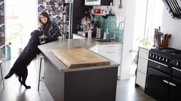 """Alexandra Zazzi och hunden Grappa trivs i köket i villan i Sävedalen: """"Just nu är det perfekt."""" Foto: Robin Aron"""
