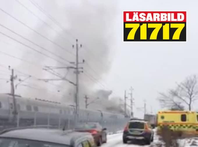 Tåget brinner och alla passagerare evakueras. Foto: LÄSARBILD
