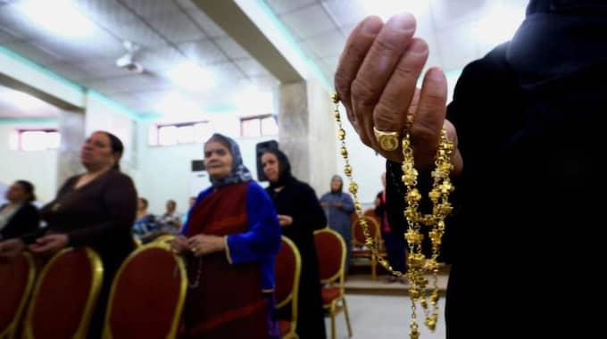 På flykt. I lördags tvingades kristna fly våldet i staden Mosul i Irak. Här ber de i en kyrka i Qaraqoush. Foto: AP