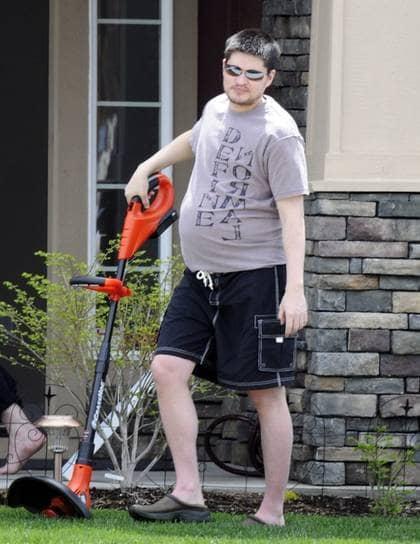 """Gravid man. Thomas Beatie, 34, trimmar gräset utanför sitt hem i Oregon, USA, i en t-shirt med texten """"Definiera normal"""". Han är den före detta kvinnan som nu är en gravid man. Foto: BULLS"""