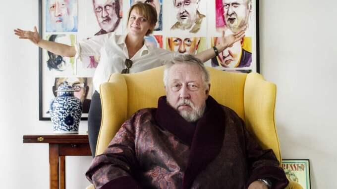 Leif GW Persson i den nya skräddarsydda rökrock som han fick av sin hustru i 70-årspresent. Tavlan i bakgrunden visar 15 ansikten av GW. I samband med sin födelsedag fick han även en löpsedel från Expressen som en hälsning. Foto: Simon Hastegård