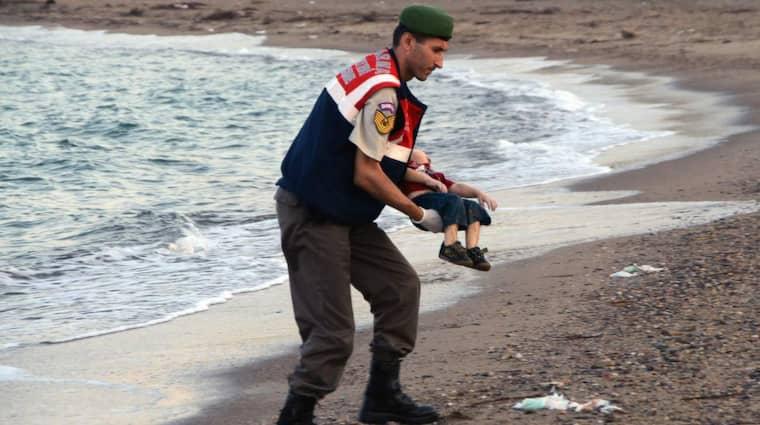En polis bär Alan Kurdis kropp på stranden i turkiska Bodrum. Foto: AP DHA