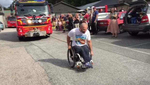 Här drar Mohammed en brandbil med bara överkroppen