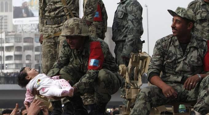 Det finns uppgifter om att 100 människor, och bland dem två barn, ska ha dödats i samband med oroligheterna. Här lyfter en demonstrant upp ett barn till en militär - barnet är dock inte skadat såvitt Expressen vet. Foto: Asmaa Waguih