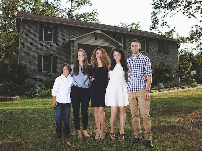Cara och hennes fyra barn framför huset som de har byggt med sina egna händer. Stolt familj!