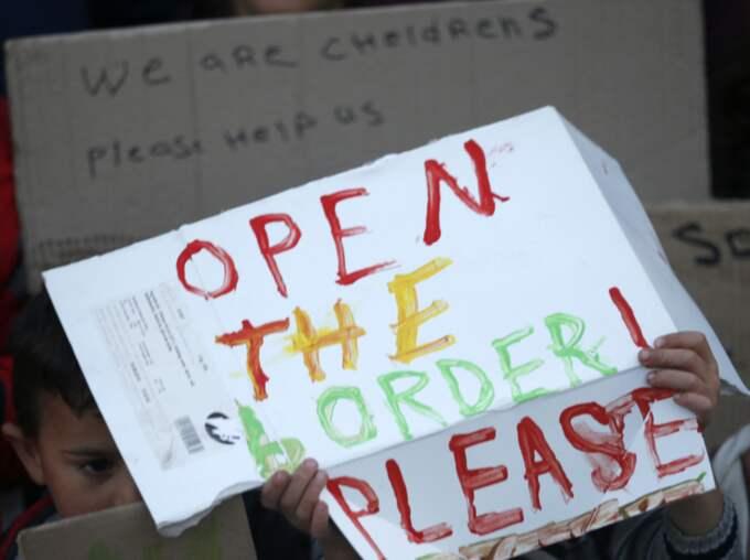 Barn håller upp skyltar i flyktinglägret i Idomeni. Foto: Darko Vojinovic / AP TT NYHETSBYRÅN