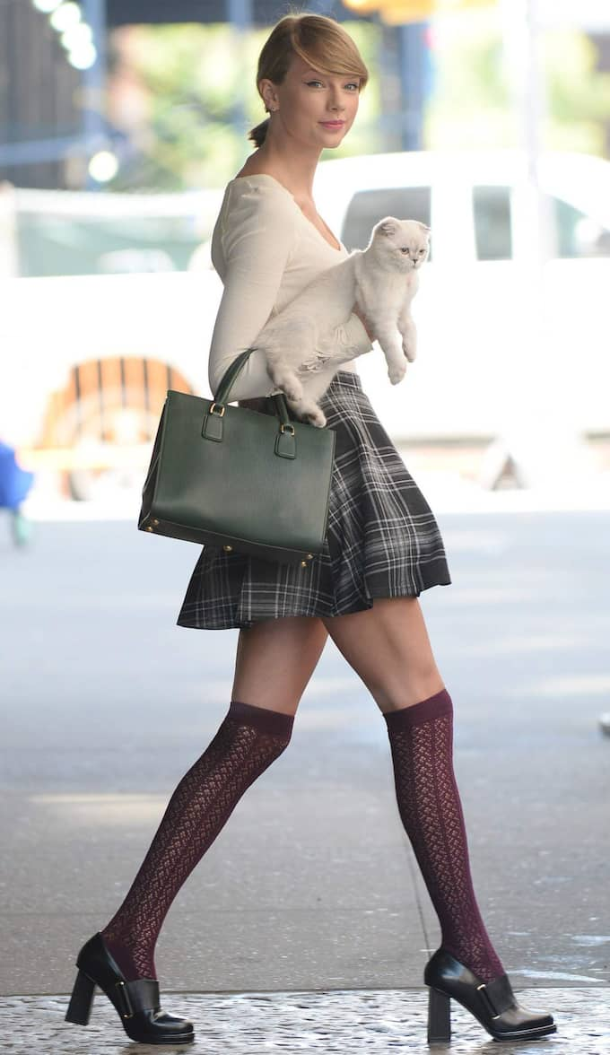 Taylor matchade sin korta kjol med vinröda knähöga strumpor och höga, lite grövre klackar. Katten Olivia fick sitta på armen.