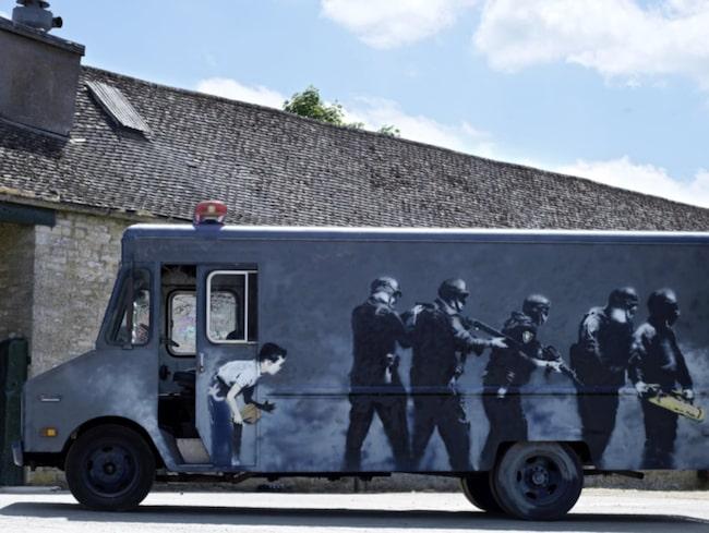 """På bilen har Banksy målat en grupp piketpoliser som letar efter Dorothy från """"Trollkarlen från Oz"""""""
