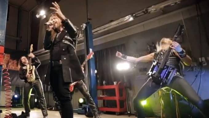 Inne i lokalen var medlemmarna i Hammerfall utklädda till verkstadsgubbar. Foto: Skärmdump