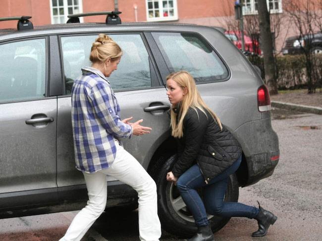 Legitimerade naprapaten Jenny Littorin visar Mikaela Älgevik (i svart jacka) att det är viktigt att arbeta med rak rygg och i stället böja på benen när man byter däcken.