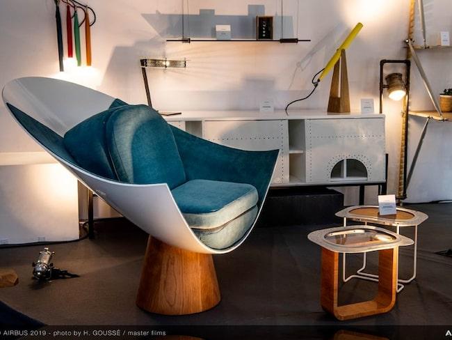 Fåtöljens stomme är en flygplansnos och borden görs av planets fönsterramar. Skåp i vit flygplansplåt.