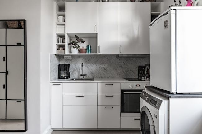...nyrenoverat kök med vita skåpsluckor och stänkskydd i carraramarmor. Spishäll, ugn, kyl med frysfack och tvättmaskin kombinerad med torktumlare.