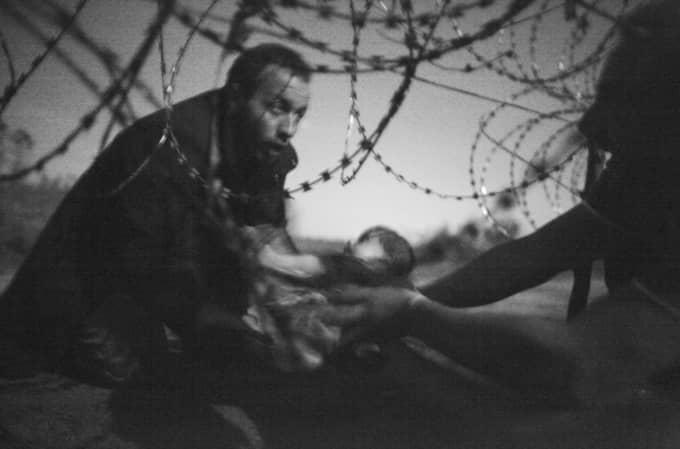 """Vinnarbilden """"Hope for a New Life"""". En man skickar en bebis genom stängslet vid den serbiska gränsen mot Ungern. Bilden är taget 28 augusti 2015. Foto: Warren Richardson"""