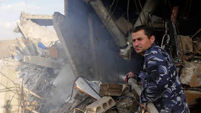 En brandman jobbar på den bombade anläggningen SSRC. Foto: Kassem Hamadé