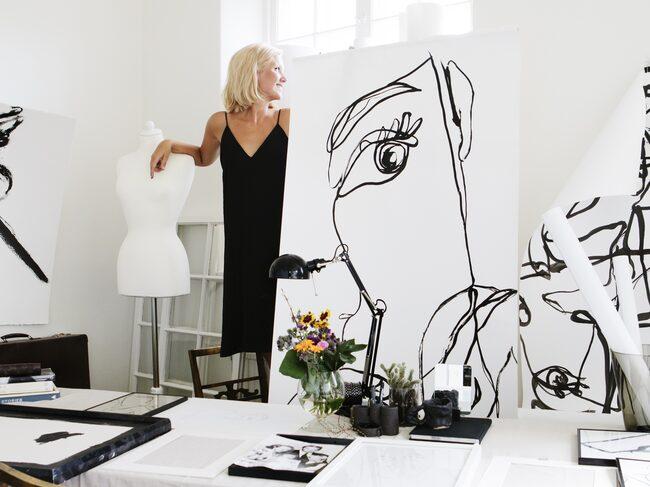 Amanda med ett av sina konstverk. Svart skrivbordslampa från Ikea.