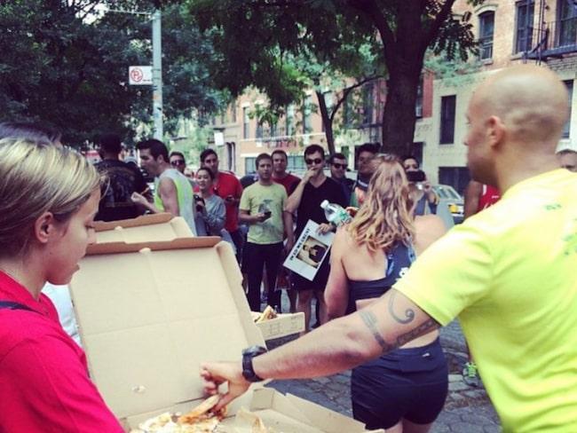 Efter att ha sprungit tre varv runt parken måste varje löpare stanna till och äta två rejäla pizzabitar.