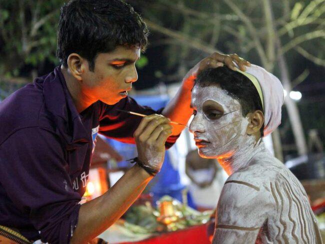 En man målas inför Theyyam-ceremonin.