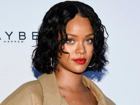 Rihanna bär sina lockar i en snygg wetlook-stil.