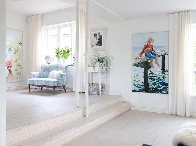 """Malin och Mikael valde att öppna upp mellan vardagsrummet och """"mellanrummet"""" för att få en känsla av ljus och rymd. Målningarna som föreställer barnen är gjorda av deras farmor Britt Jönsson."""