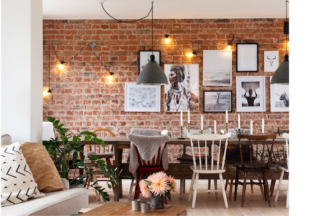 Tegel, tegel på väggen där. I matrummet togs den gamla tegelväggen fram vilket gav hela rummet sin speciella karaktär. Bordet har Filip tillverkat och de blandade stolarna är fyndade på loppis. Det två lamporna som kommer från en granne har My målat om.