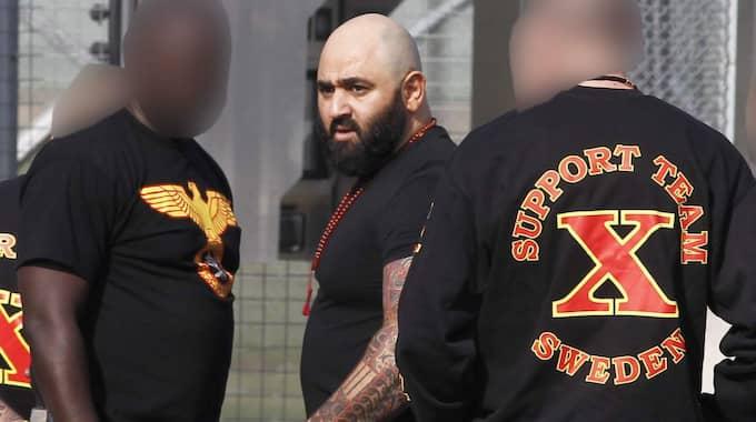 Bandidostoppen Mehdi Seyyed skriver på en bok med sin advokat. Han är bland annat dömd för att ha beställt två bilbomber. Foto: Richard Ström/Expressen