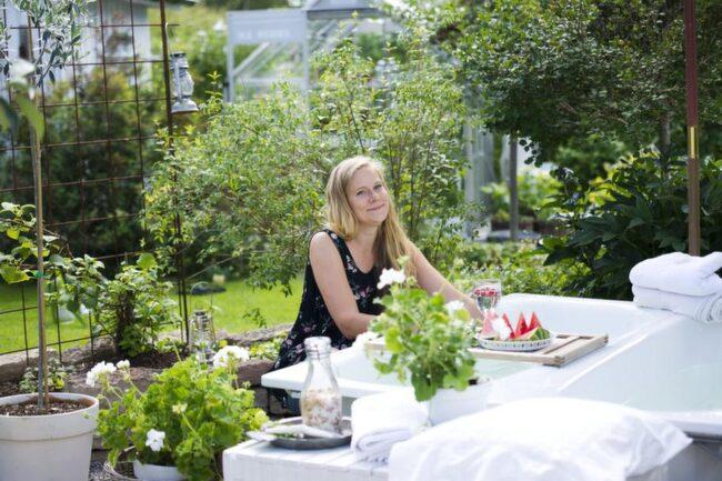 Hanna bloggar om hantverk. Här sitter hon i sin trädgård.