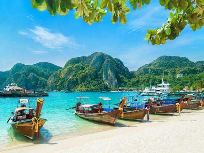 Longtailbåtar vid Tonsai Beach Bay på Phi Phi Island. Hit åker många för att snorkla och sola.