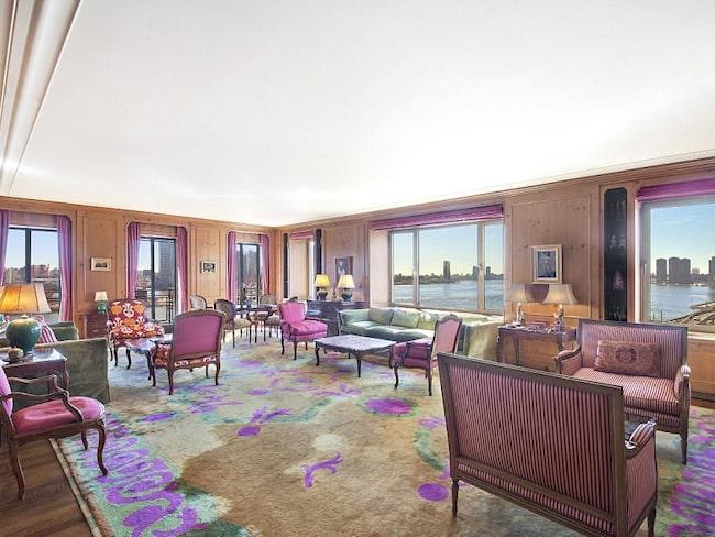 Det stora vardagsrummet inrett med lila detaljer och en fantastisk utsikt övr East river i New York.