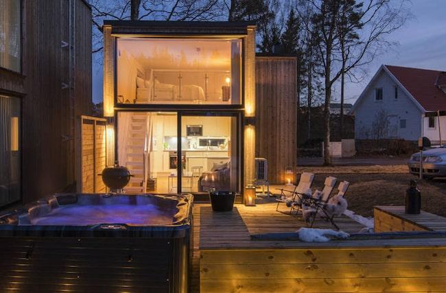 Inbjudande entré med fasadbelysning och träpanel. Vidare från ytterdörren sträcker sig en trätrall runt huset till framsidan och uteplatsen.