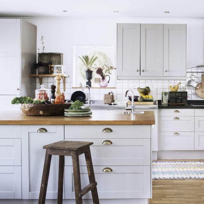"""Inred köket med en grå kulör som bas och jobba med svarta detaljer, det ger både en klassik och elegant stil. Lägg till varma färger som mossgrönt och ockragult. Köksluckorna från Ikea är av modellen Grytnäs. De övre skåpen är ommålade i en grå nyans som är lik """"Lamp room gray no 88"""" från Farrow & Ball. De mässingsfärgade handtagen är från Ikea och heter Fågleboda."""