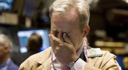 En bild av den finansiella krisen i USA. En bekymrad aktiehandlare på New York-börsen och en minst lika bekymrad George W Bush efter kongressens nej till krispaketet. Foto: AP