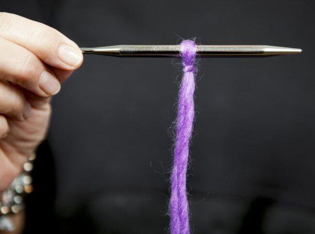 LÄGGA UPP<br>1. Gör en ögla av garnet och trä den på stickan. Dra i båda garnändarna så dras öglan åt.