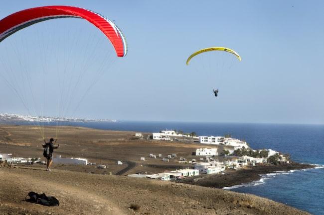 Skärmflygarna springer med lätta steg tills vinden lyfter dem över Playa Quemada.
