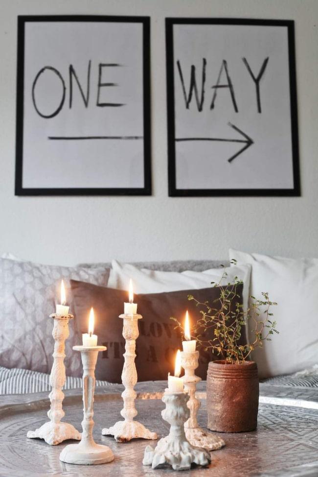 Vackert stilleben med ljusstakar i olika höjder på ett härligt brickbord. Tavlan har Jennifer gjort själv och ändrar gärna text när hon kommer på nya citat eller ord.