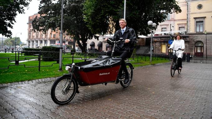 Klimat- och vice statsminister Isabella Lövin (MP) och biträdande finansminister Per Bolund (MP) cyklar på elcyklar utanför Rosenbad i Stockholm. Foto: / TT NYHETSBYRÅN