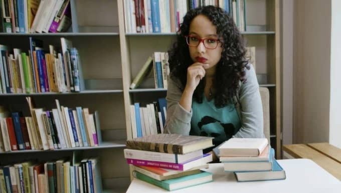 """BLAND SINA VÄNNER. Biblioteket är bland det bästa Afrah Nasser vet. Det är där hennes vänner, böckerna, finns. """"De är lojala, vänliga och ett bra sällskap. De finns alltid här för mig"""", säger hon. Foto: Henrik Jansson"""