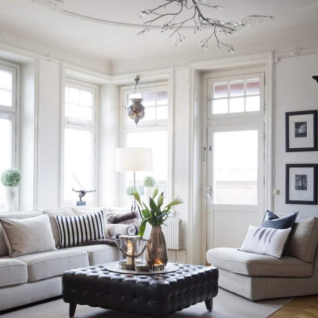 Till den stora, engelska soffan matchar Ikeas loungefåtöljer i samma färgnyans. Likadana teleskoplampor med vita skärmar på båda sidor soffan skapar symmetri. I taket hänger en grenlampa från Ilva.