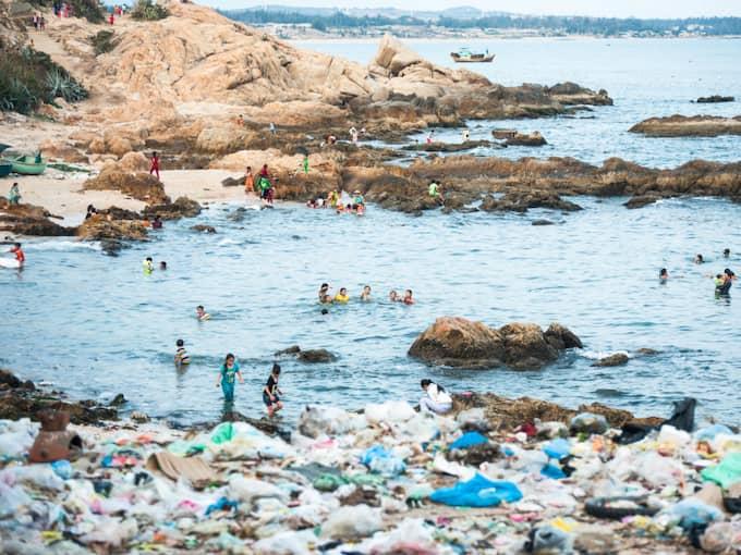 Barn badar mot en fond av uppspolade sopor. Plast i haven är bara ett sätt människan förstört och omskapat världen på. Foto: Nguyen Quoc Thang / SHUTTERSTOCK