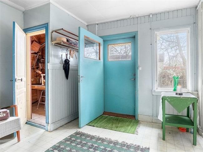 I entrén möts man direkt av en stor och rymlig hall. Plastmatta på golv, målade och panelade väggar. Trappan till källaren når man från hallen.