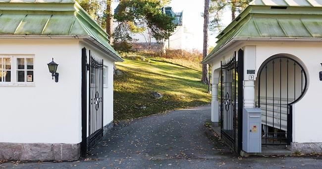 Infarten till tomten flankeras av två vitputsade grindstugor i samma stil som huvudbyggnaden med väldiga gjutjärnsgrindar.