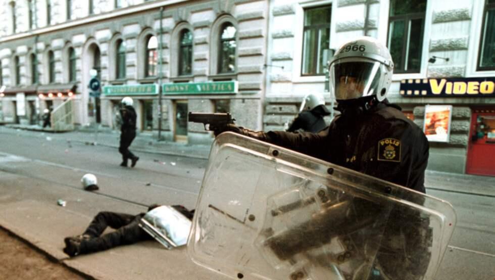 ÅRETS BILD 2001. En polisman ligger skadad på marken efter stenkastning och en annan har dragit sin pistol. Foto: Larseric Linden